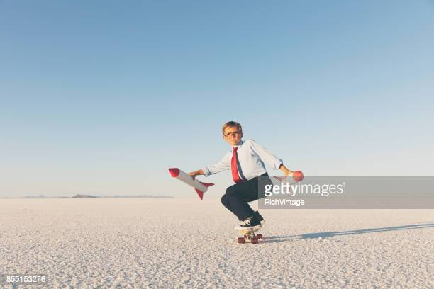 business boy holding rockets on skateboard - kick off stock pictures, royalty-free photos & images