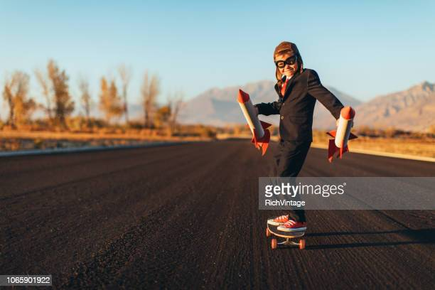 business boy holding rockets standing on skateboard - launch event stock pictures, royalty-free photos & images