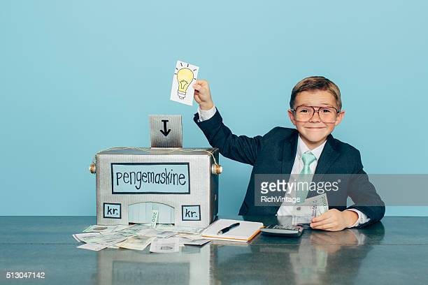 business boy puts ideas in machine and makes danish money - contraptie stockfoto's en -beelden