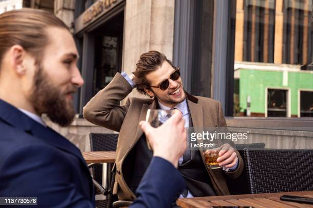 business break - two young businessmen taking a break in central london - high society stock pictures, royalty-free photos & images