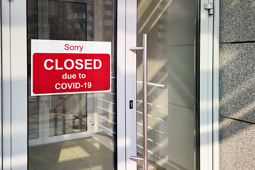 Business center closed due to COVID-19, sign with sorry in door window. Stores, restaurants, offices, other public places temporarily closed 1217768037