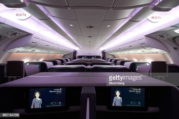 Business class seats of a Singapore Airlines Ltd Airbus SE A380 aircraft with refitted cabins are seen during a media tour at Changi Airport in...