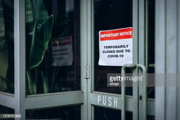 """business closed down signage putting onto a store window saying """"temporarily closed due to covid-19"""" during the covid-19 pandemic - government shutdown stock pictures, royalty-free photos & images"""