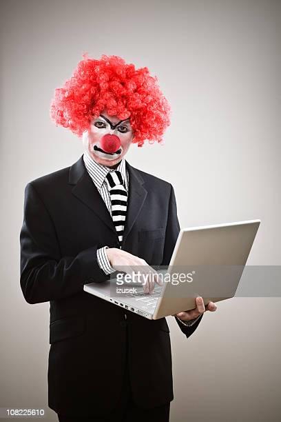 Business-Clown Tippen auf Laptop