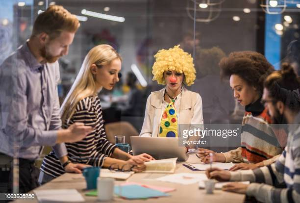 business clown using laptop on a meeting with her colleagues. - idiots stock pictures, royalty-free photos & images