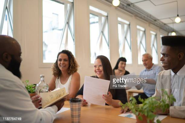 business colleague (including special needs woman) discussing new ideas at modern startup office - differing abilities female business stock pictures, royalty-free photos & images