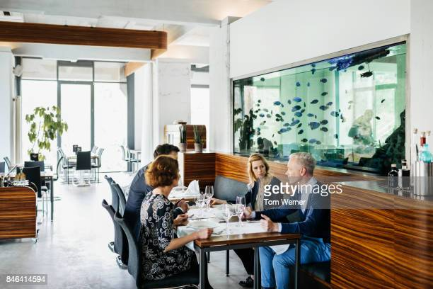 Business Colleague Eating Lunch Together In Contemporary Restaurant