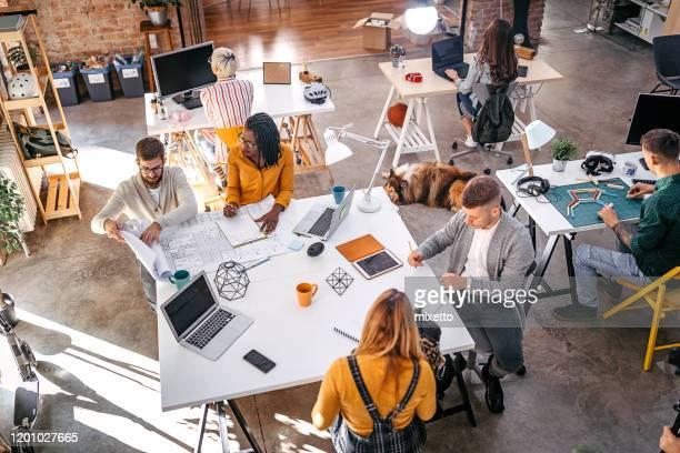 geschäftskollegen analysieren neues projekt im büro - gestalterischer beruf stock-fotos und bilder