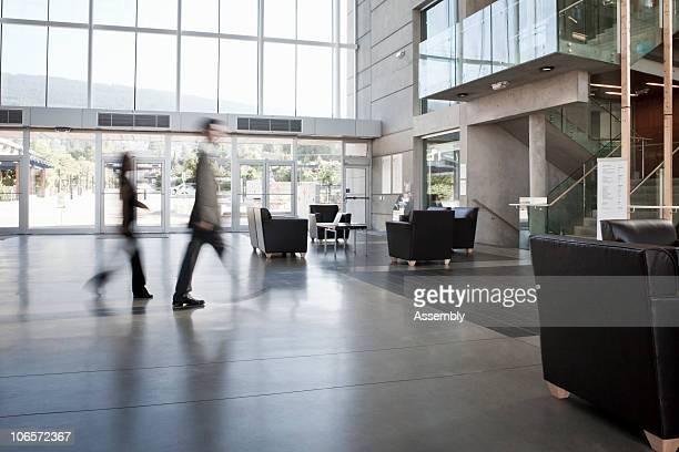 business colleagues blurred walking through office - hotel lobby stock pictures, royalty-free photos & images