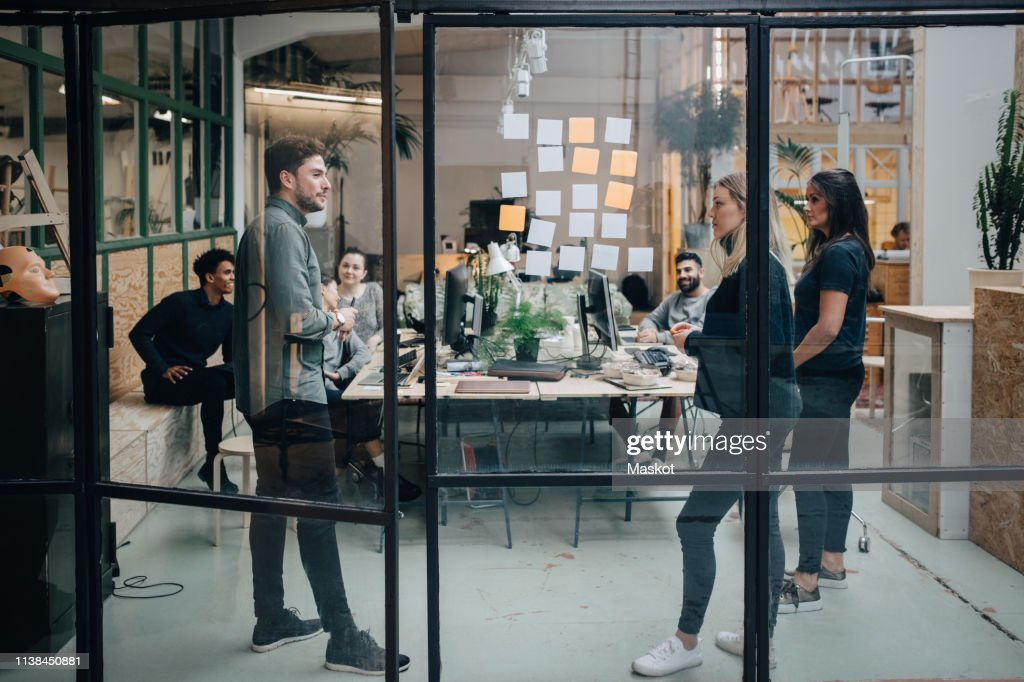 Business colleagues brainstorming in meeting at office seen through glass wall : Stock Photo