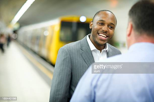 business colleagues chatting on the subway platform