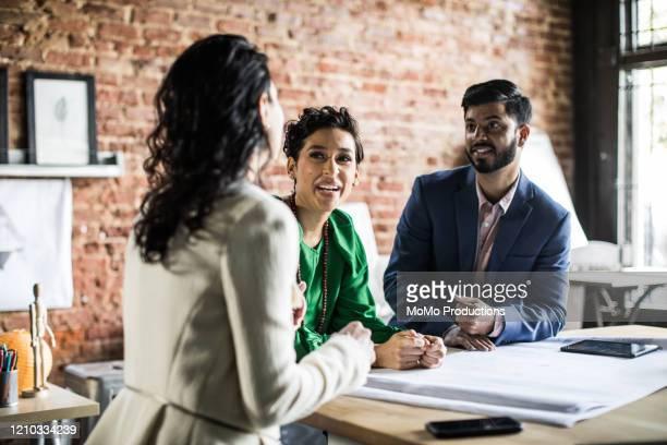 business colleagues discussing architecture project in office - tenue d'affaires photos et images de collection