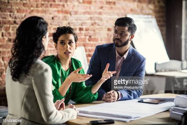 business colleagues discussing architecture project in office - three people stock pictures, royalty-free photos & images