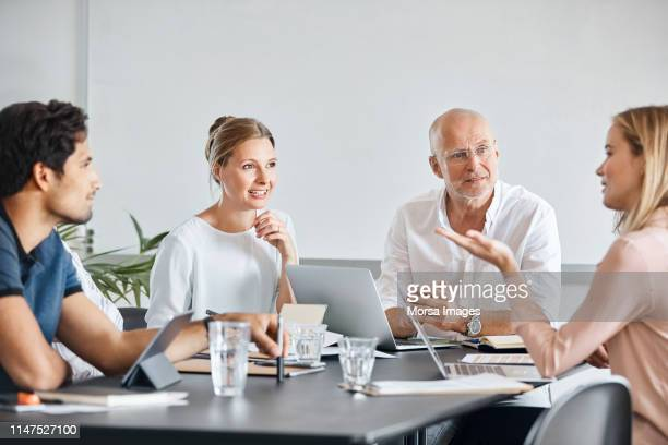 business colleagues discussing at conference table - scandinavia stock pictures, royalty-free photos & images