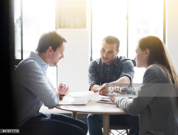 Business colleagues discussing at desk in office
