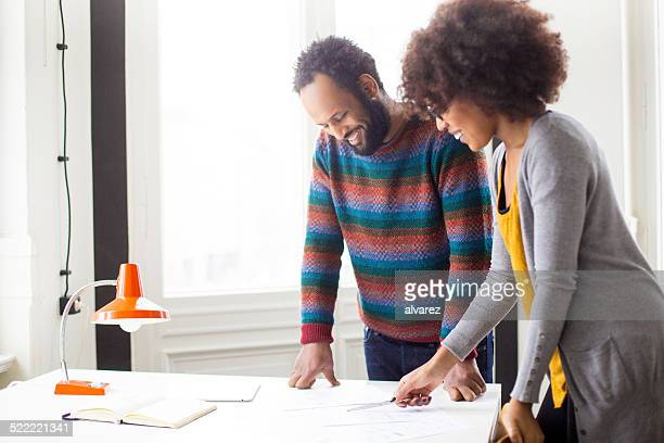 business colleagues discussing documents in the office - founder stock pictures, royalty-free photos & images