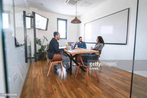 colegas de negócios discutindo ideias na sala de conferências - visão geral - fotografias e filmes do acervo