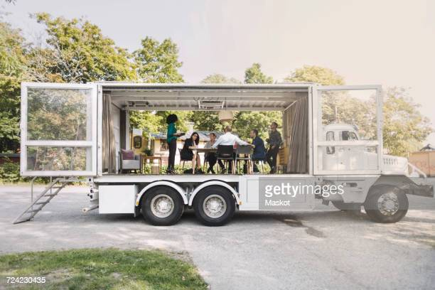 Business colleagues discussing in portable office truck at park