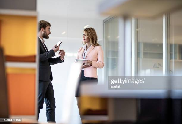 business colleagues discussing in the corridor - business finance and industry stock pictures, royalty-free photos & images