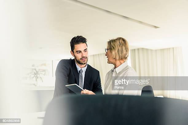 Business colleagues discussing over digital tablet