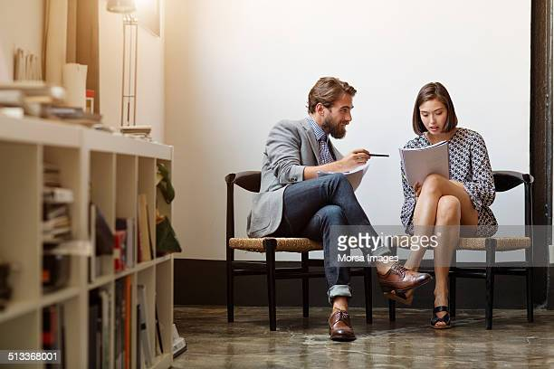 Business colleagues discussing over documents