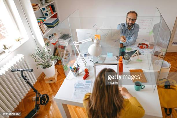ガラス壁の仕切りに関する計画について議論するビジネス仲間 - アクリル ストックフォトと画像