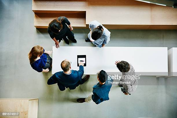 business colleagues discussing project in office - business strategy stock pictures, royalty-free photos & images