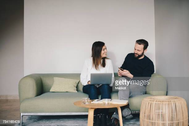 Business colleagues discussing while sitting on sofa against white wall at office lobby