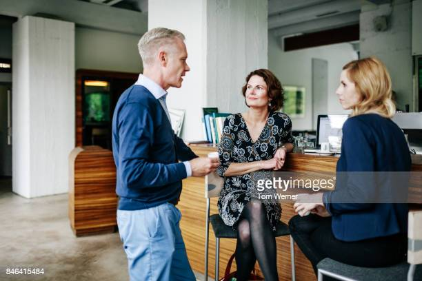 Business Colleagues Discussing Work Over Coffee At Restaurant Bar