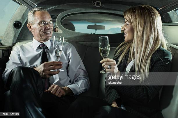 Collègues de boire du champagne dans une limousine.