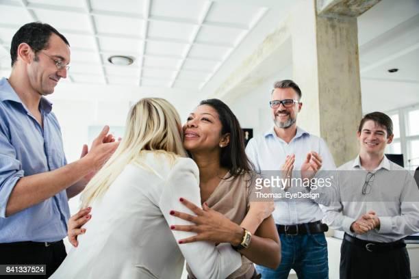 geschäftskollegen umarmen einander feiert erfolgreichen pitch - kleine personengruppe stock-fotos und bilder