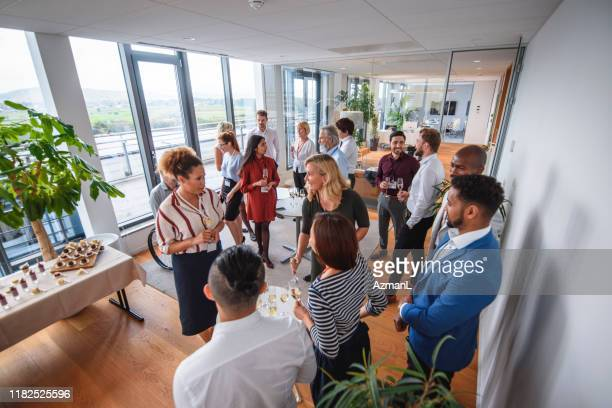 business colleagues enjoying sparkling wine and conversation - work party stock pictures, royalty-free photos & images
