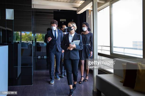 business colleagues entering the office wearing protective face masks - riapertura foto e immagini stock