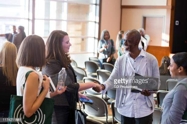 business colleagues greet during conference - town hall stock pictures, royalty-free photos & images