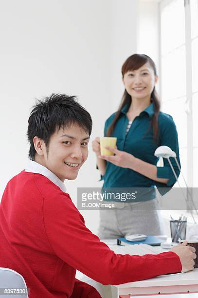 Business colleagues having break in small office, smiling