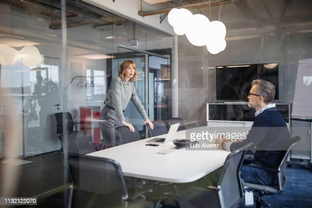 business colleagues having discussion in board room - plano americano - fotografias e filmes do acervo