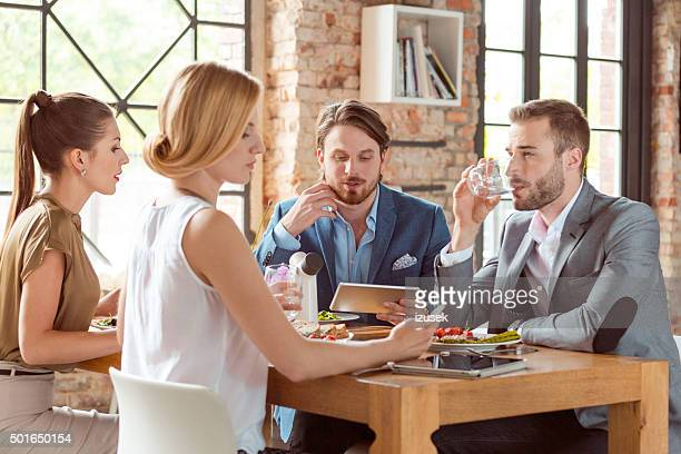 Business colleagues having lunch, bearded man using digital tablet