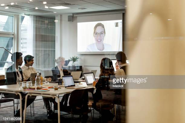 business colleagues having meeting through video conference in board room at workplace - テレビ会議 ストックフォトと画像
