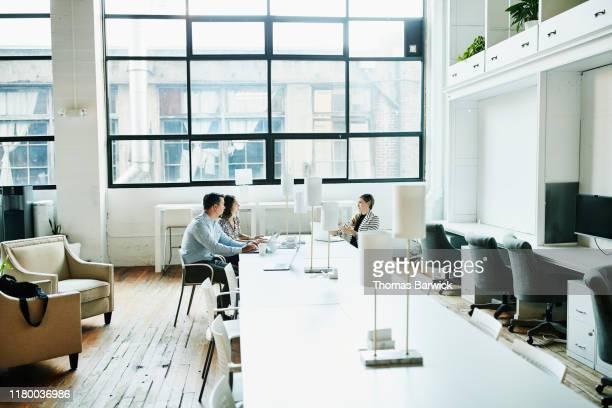business colleagues having project meeting in coworking office - finanzas y economía fotografías e imágenes de stock