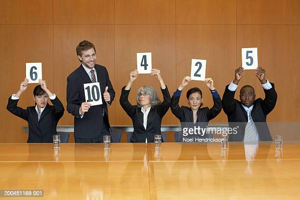 business colleagues holding up cards with numbers, man standing - scoring stock pictures, royalty-free photos & images