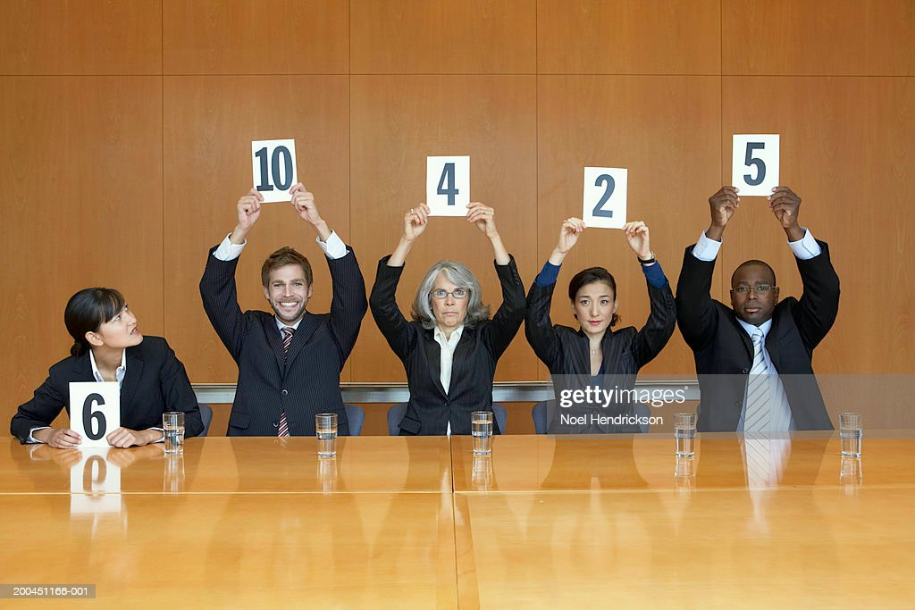 Business colleagues holding up cards with numbers : Stock Photo