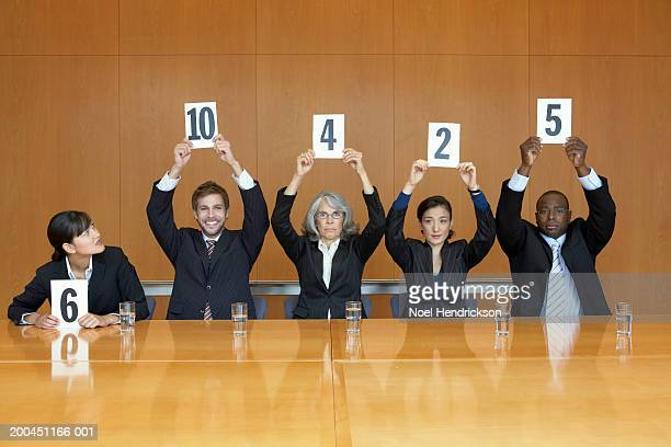 business colleagues holding up cards with numbers - scoring stock pictures, royalty-free photos & images