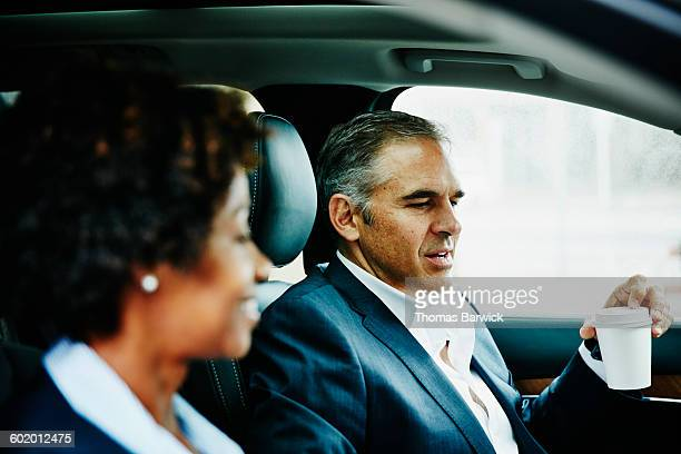 Business colleagues in discussion in car