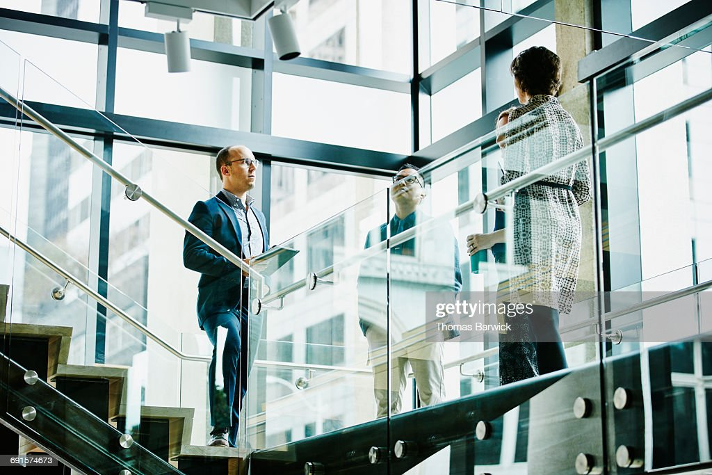 Business colleagues in discussion on office stairs : Stock Photo