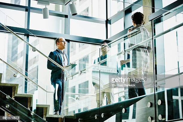 business colleagues in discussion on office stairs - man made structure stock pictures, royalty-free photos & images