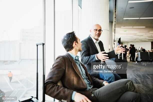 Business colleagues in discussion while waiting for flight in airport