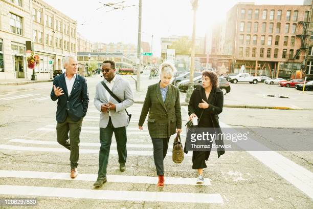 business colleagues in discussion while walking to work on city street - diversity stock pictures, royalty-free photos & images
