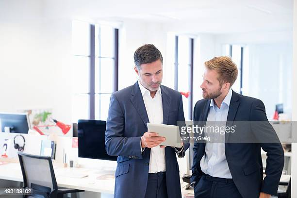business colleagues in impromptu discussion using digital tablet - face to face stock pictures, royalty-free photos & images