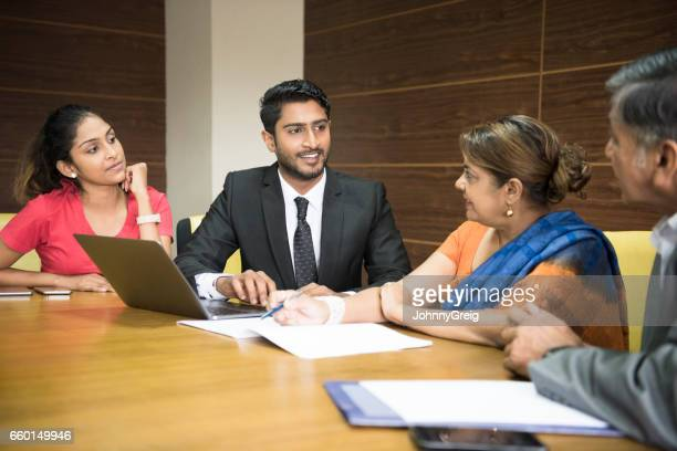 Business colleagues in meeting room, young man with laptop