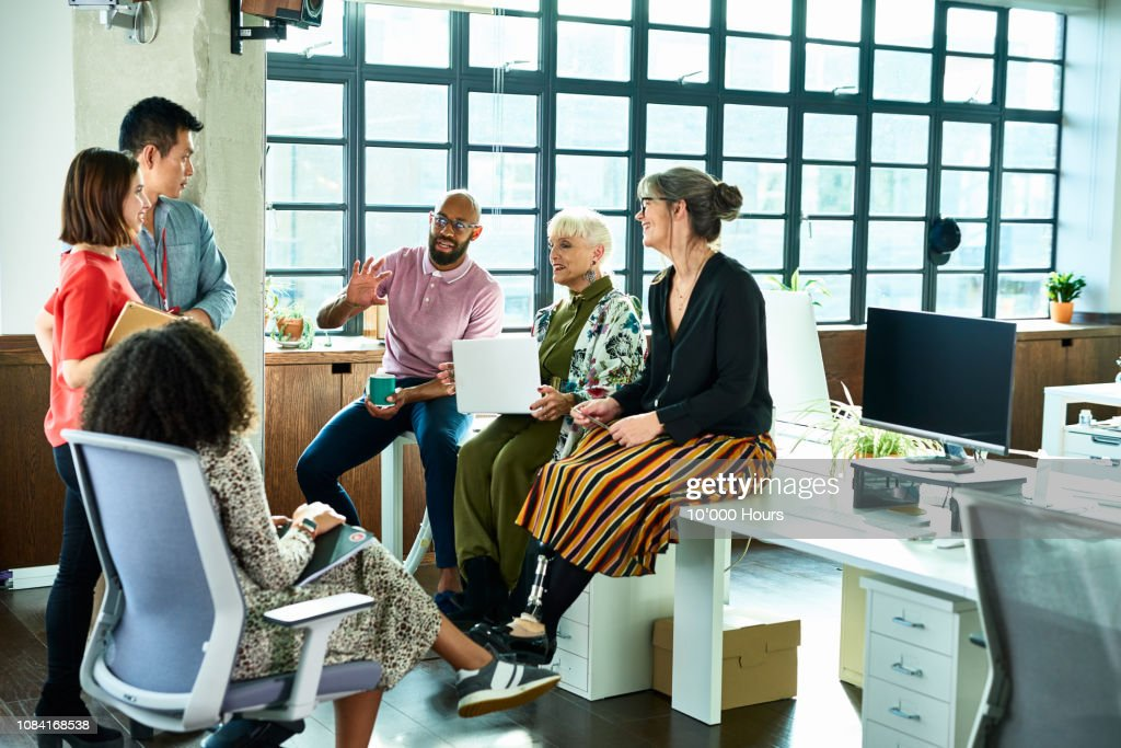 Business colleagues in meeting with female amputee sitting on desk : Stockfoto